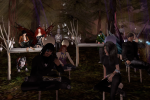 A group of machinima learners sit in a night forest environment listening to a presentation, watching videos and chatting amongst themselves.